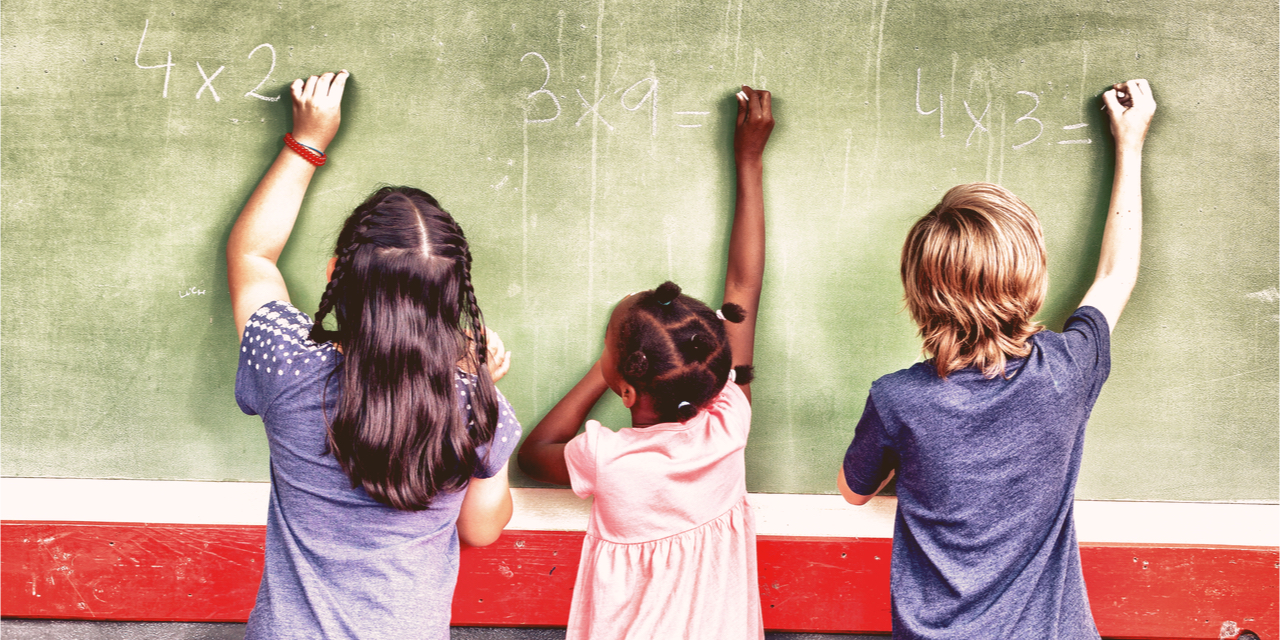 Children multiplying on a black board.
