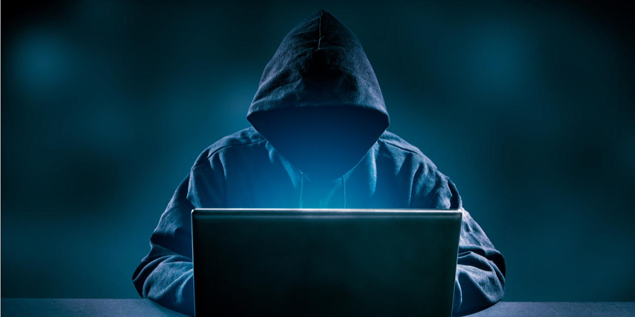Hacker in hoodie at laptop