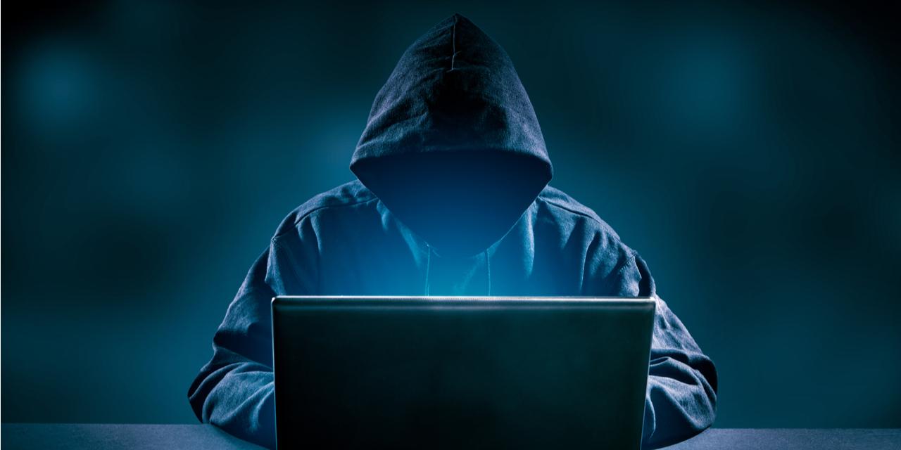 Hacker in hoodie at laptop