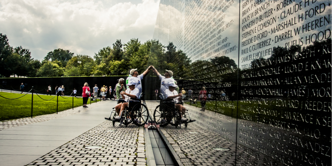 Individuals pointing to names on Vietnam War memorial wall
