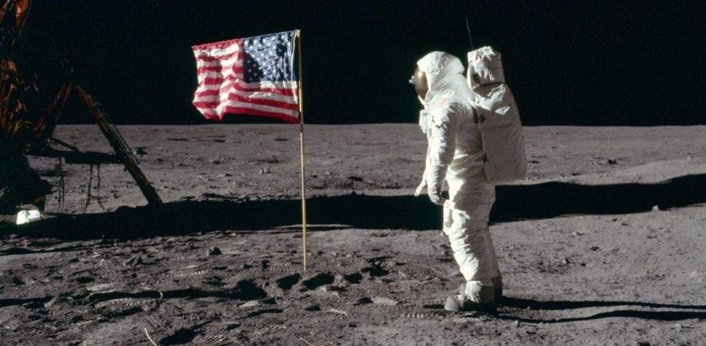 Astronaut facing flag on moon