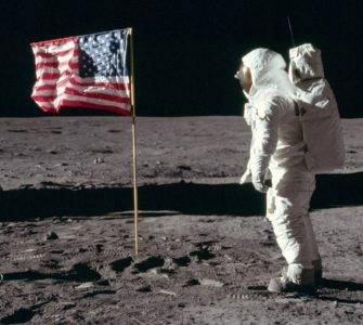 Astronaut facing flag on moon
