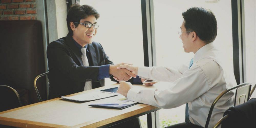 Men shaking hands across table