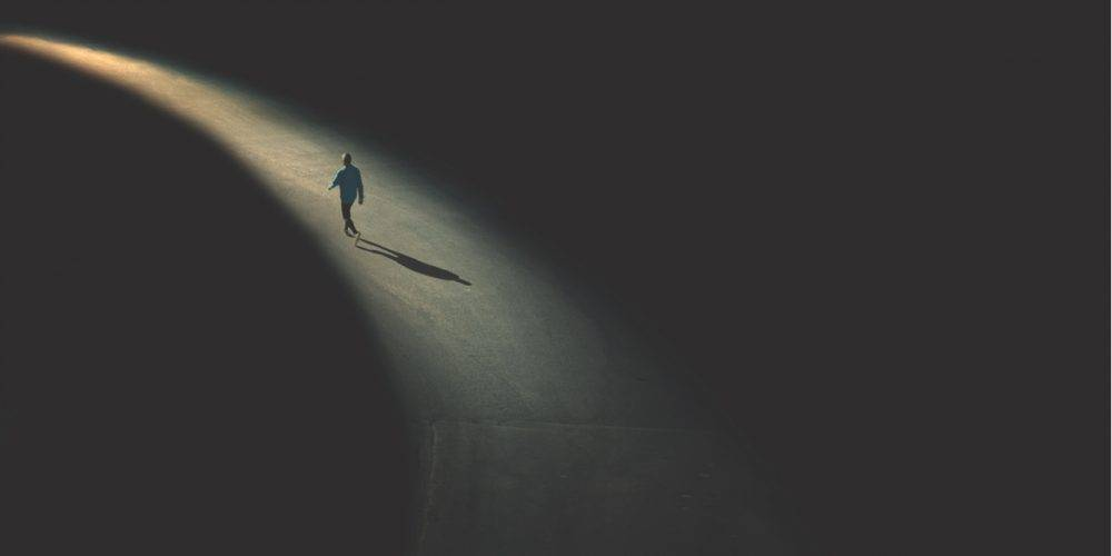 Man walking on lighted path to destination