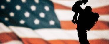 American flag background, soldier holding up little girl - shutterstock_368985278