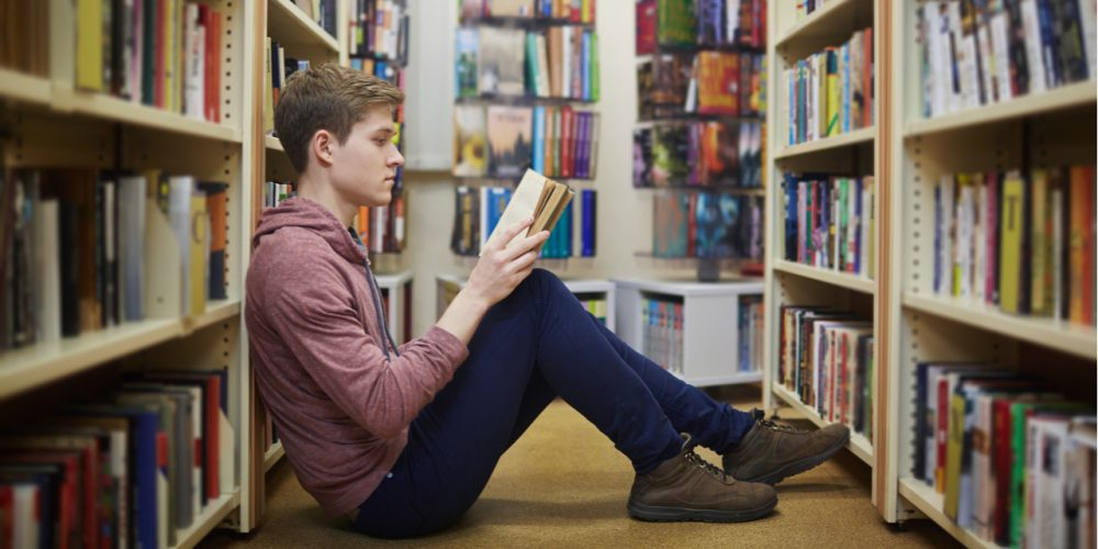Young man reading in library